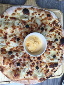 Banana & cheese pizza topped with cinnamon and blueberries. Served with mango ice cream.